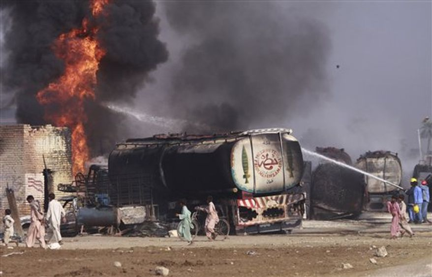 Pakistani firemen try to extinguish the blaze on the still smoldering oil trucks in Shikarpur, southern Pakistan on Friday Oct. 1, 2010. Suspected militants set ablaze at least 27 tankers carrying fuel for U.S. and NATO troops in Afghanistan on Friday, police said. (AP Photo/Aaron Favila)