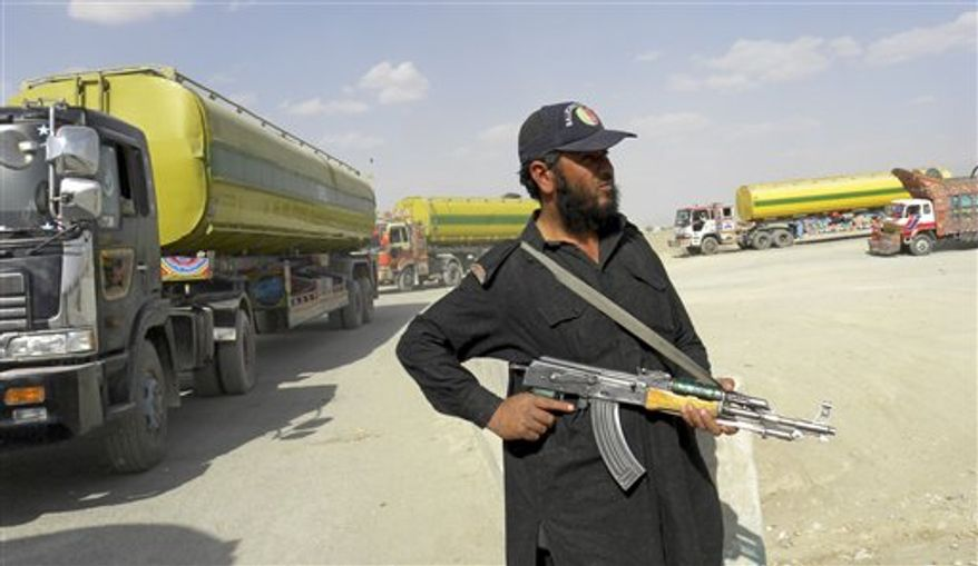 A Pakistani border guard stands alert as NATO trucks carry fuel, proceed to neighboring Afghanistan at Pakistani border post Chaman on Friday, Oct. 1, 2010. Pakistan closed the Khyber Pass supply route in northwest for U.S. and NATO troops in Afghanistan after a coalition helicopter attack mistakenly killed three Pakistani soldiers at a border post, raising tensions in a vital relationship for both Islamabad and Washington. (AP Photo/Shah Khalid)