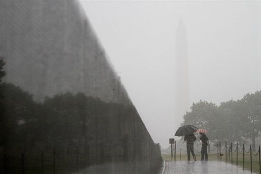 The outline of the Washington Monument can barely be seen from the Vietnam Veterans Memorial in Washington, Thursday, Sept. 30, 2010, during a heavy rain storm. (AP Photo/Jacquelyn Martin)