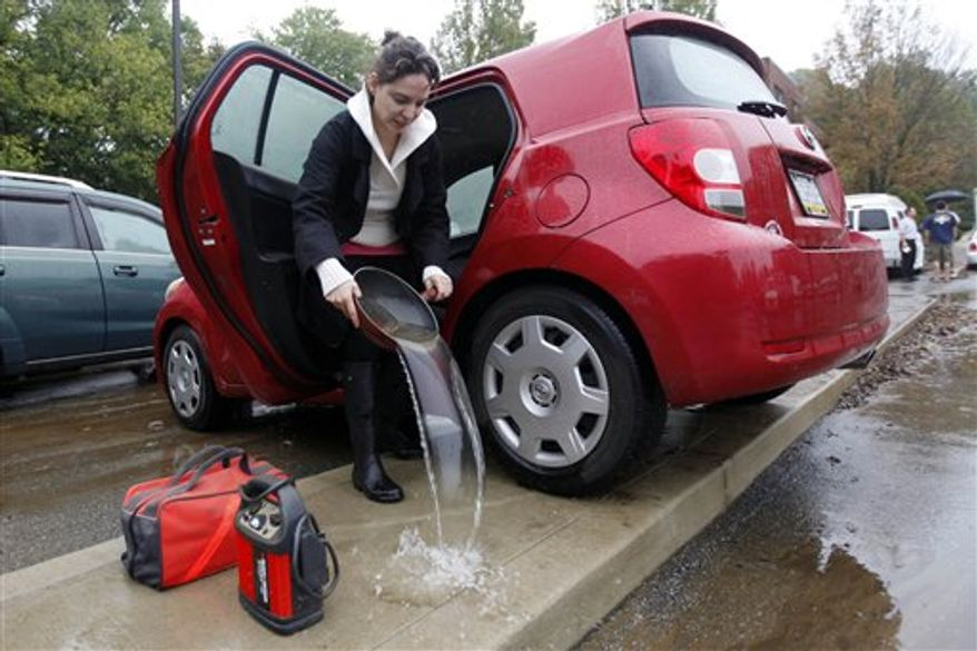 Amel Sincere empties out her car after receded floodwaters submerged the parking lot of the Waterford Apartments in Havertown, Pa., Friday, Oct. 1, 2010. (AP Photo/Matt Rourke)