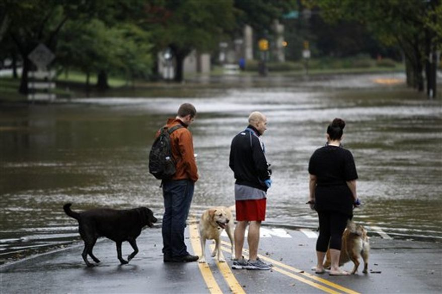 People and their dogs stand before floodwaters from the Schuylkill River that submerged a section of Kelly Drive in Philadelphia, Friday, Oct. 1, 2010. (AP Photo/Matt Rourke)