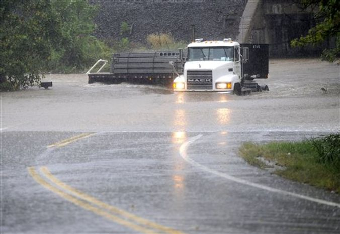 A truck makes its way through a rising Stemmers Run on Golden Ring Road in east Baltimore County, Md. A massive rainstorm drenched the East Coast from the Carolinas to Maine on Thursday, washing out commutes and wiping away months of dry weather. (AP Photo/Baltimore Sun, Jed Kirschbaum)