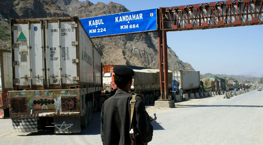A Pakistani border guard stands near Afghanistan-bound NATO trucks parked on the roadside in Pakistani tribal area of Khyber on Friday, Oct. 1, 2010. Pakistan closed the Khyber Pass supply route for U.S. and NATO troops in Afghanistan on Thursday after a coalition helicopter attack mistakenly killed three Pakistani soldiers at a border post, raising tensions in a vital relationship for both Islamabad and Washington. (AP Photo/Qazi Rauf)
