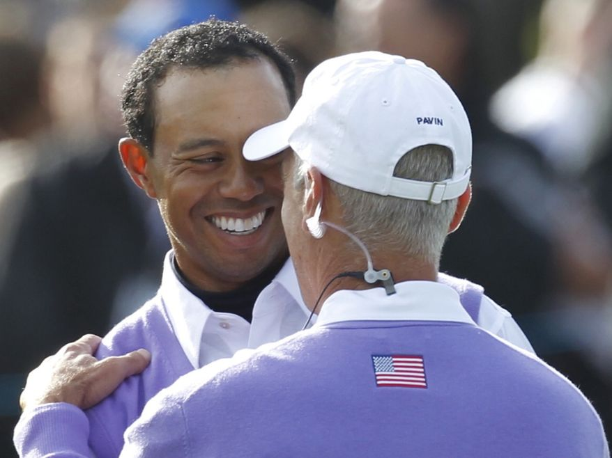 U.S. team captain Corey Pavin, right, and player Tiger Woods react after Woods finished his round on the second day of the 2010 Ryder Cup golf tournament at the Celtic Manor Resort in Newport, Wales, Saturday, Oct. 2, 2010. (AP Photo/Alastair Grant)