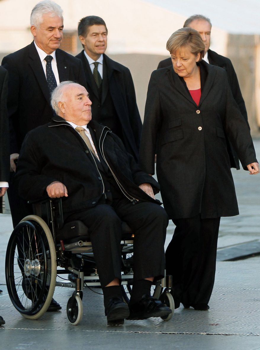 Former German Chancellor Helmut Kohl and Chancellor Angela Merkel arrive at the Reichstag in Berlin on Sunday for celebrations marking the 20th anniversary of Germany's reunification. (Associated Press)