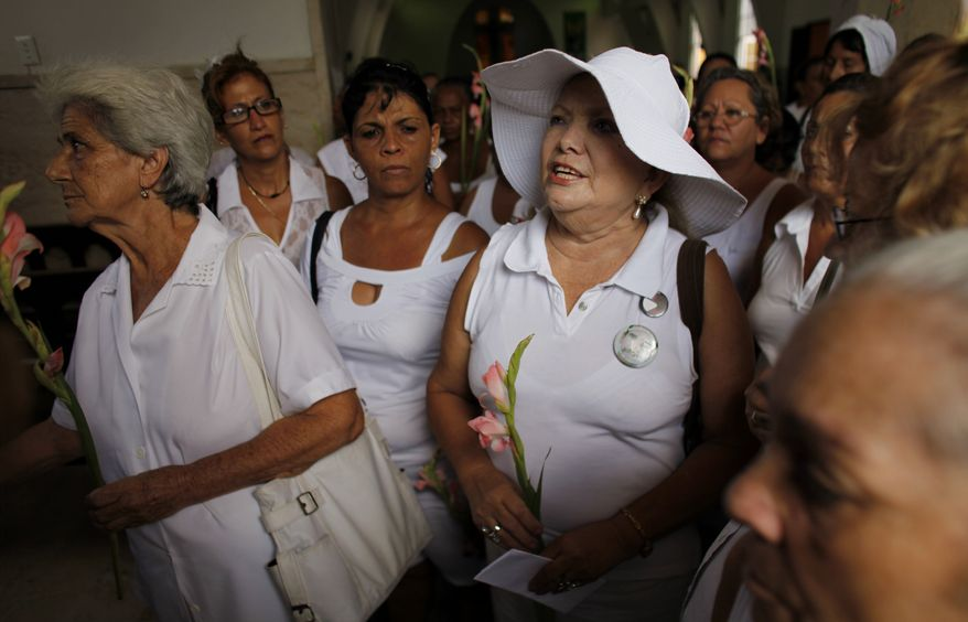** FILE ** Laura Pollan (right), leader of the Cuban female dissident group Ladies in White, prays during a Mass in Havana, on Sunday, Sept. 19, 2010. Cuba's Roman Catholic Church on the previous Friday revealed the names of four more political prisoners to be released into exile in Spain. (AP Photo/Javier Galeano)