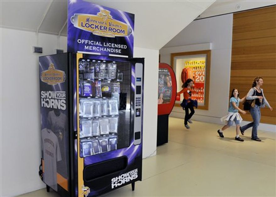 A visitor to the Mall of America walks by a Minnesota Vikings NFL football team merchandise vending machine Thursday, Sept. 30, 2010, in Bloomington, Minn. Indianapolis-based MainGate, Inc. has installed the vending machine at Mall of America with hopes that it will be profitable and the idea will catch on with its other six teams.  (AP Photo/Jim Mone)