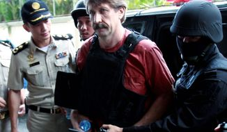 Suspected Russian arms smuggler Viktor Bout wears a bulletproof vest Monday as he arrives at a Bangkok court for a hearing that could determine his extradition to the U.S. (Associated Press)