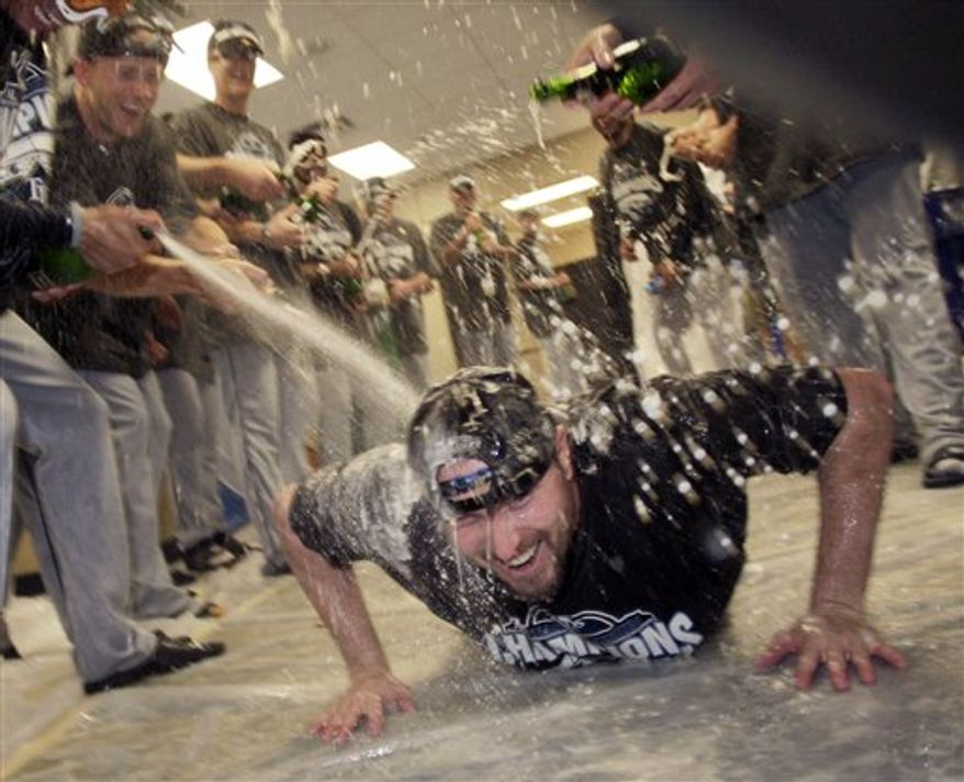 Tampa Bay Rays relief pitcher Chad Qualls slides on the clubhouse floor as he is doused with champagne after winning the American League East championship following a 3-2 win over the  Kansas City Royals in a baseball game Sunday, Oct. 3, 2010 in Kansas City, Mo. (AP Photo/Charlie Riedel)