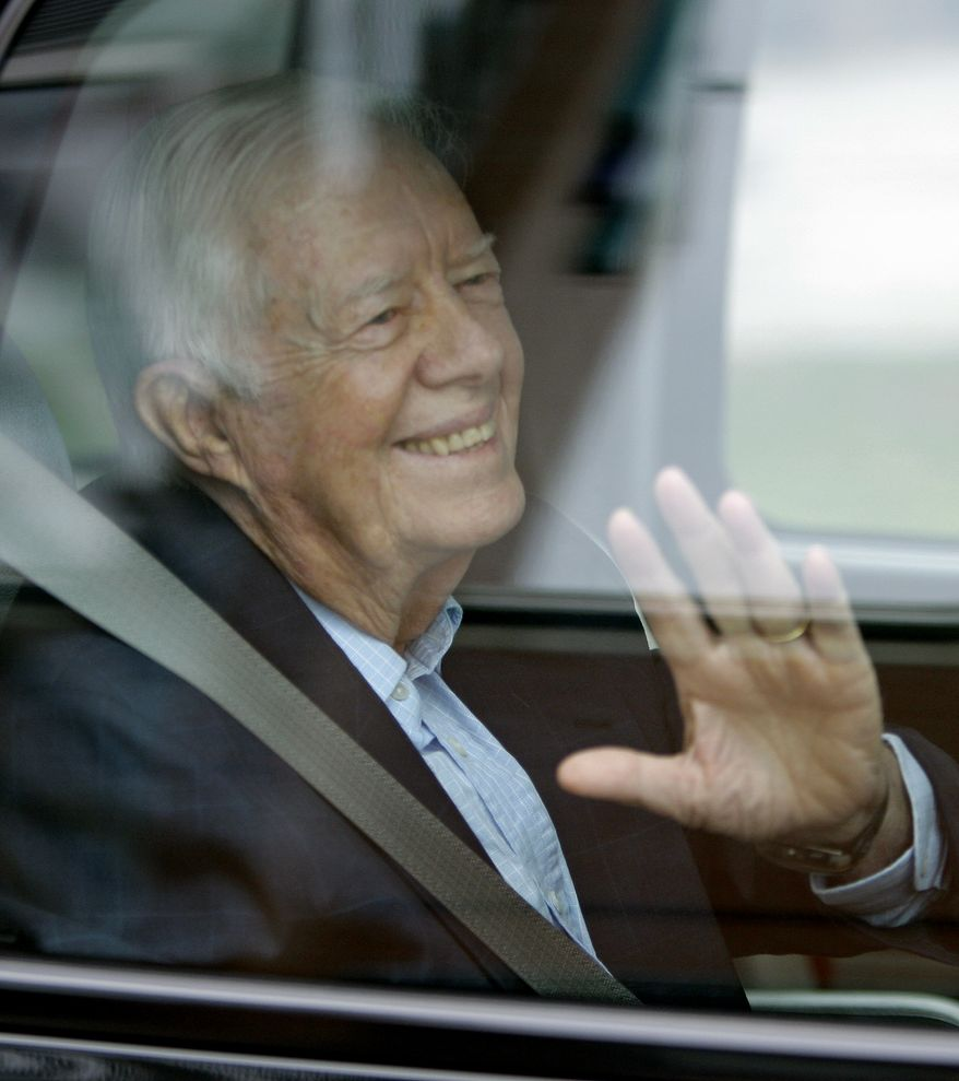 Former President Jimmy Carter waves from a vehicle as he leaves MetroHealth Hospital Thursday, Sept. 30, 2010, in Cleveland. Mr. Carter left the hospital where he spent two days recovering from a viral infection doctors say likely gave him stomach problems. (AP Photo/Tony Dejak)