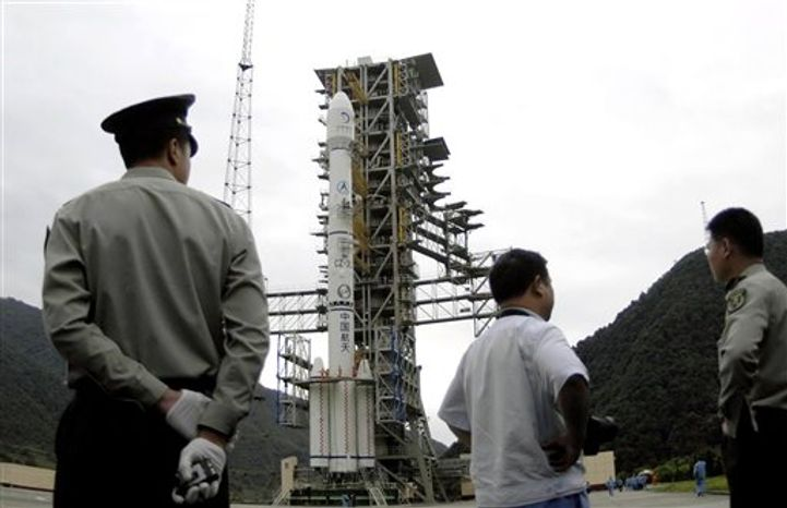 In this Saturday, Sept. 25, 2010 photo, workers stand near the Long March 3C rocket with the Chang'e II lunar probe satellite loaded on its head on the launch pad at the Xichang Satellite Launch Center in Xichang in southwest China's Sichuan province. China's space ambitions are forging ahead with plans to launch the country's second unmanned lunar probe this weekend. (AP Photo)