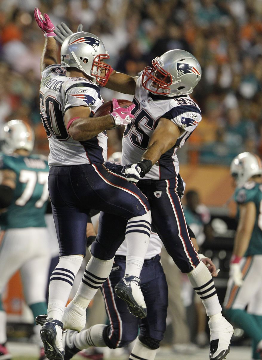 ASSOCIATED PRESS New England Patriots linebacker Rob Ninkovich (50) celebrates with linebacker Tully Banta-Cain (95) after Ninkovich intercepted a pass intended for Miami Dolphins running back Patrick Cobbs in the second quarter during an NFL football game in Miami, Monday, Oct. 4, 2010.