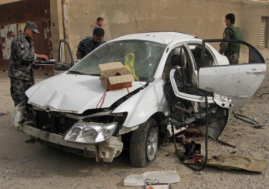 Iraqi security forces inspect a damaged car at a bombing site in Baghdad on Monday, Oct. 4. 2010. Police say the roadside bombing targeted the convoy of a deputy minister in Iraq's government, killing the minister's bodyguard and injuring at least seven people. (AP Photo/Hadi Mizban)