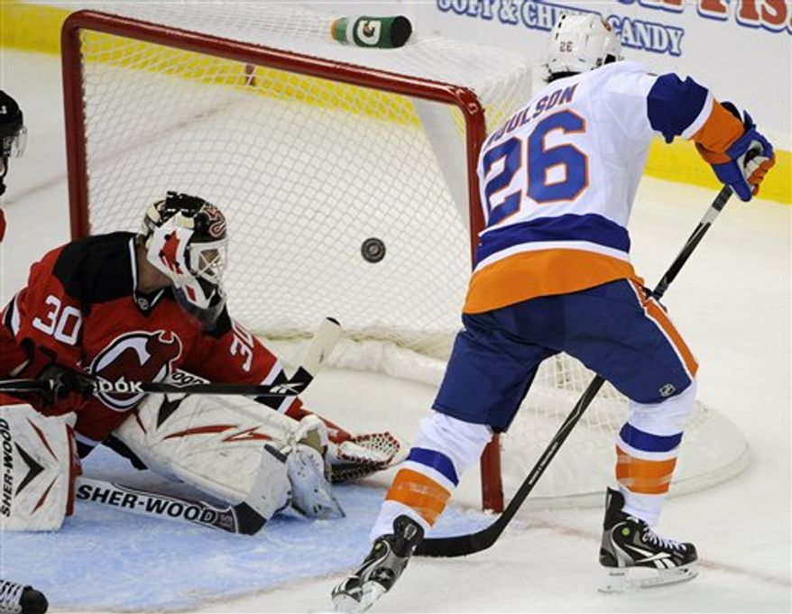New Jersey Devils' Patrik Elias, right, of the Czech Republic, attempts to get his stick on the puck as he is checked by New York Islanders' Andrew MacDonald in front of Islanders goaltender Dwayne Roloson, left, during the first period of an NHL preseason hockey game Friday, Oct. 1, 2010, in Newark, N.J. (AP Photo/Bill Kostroun)