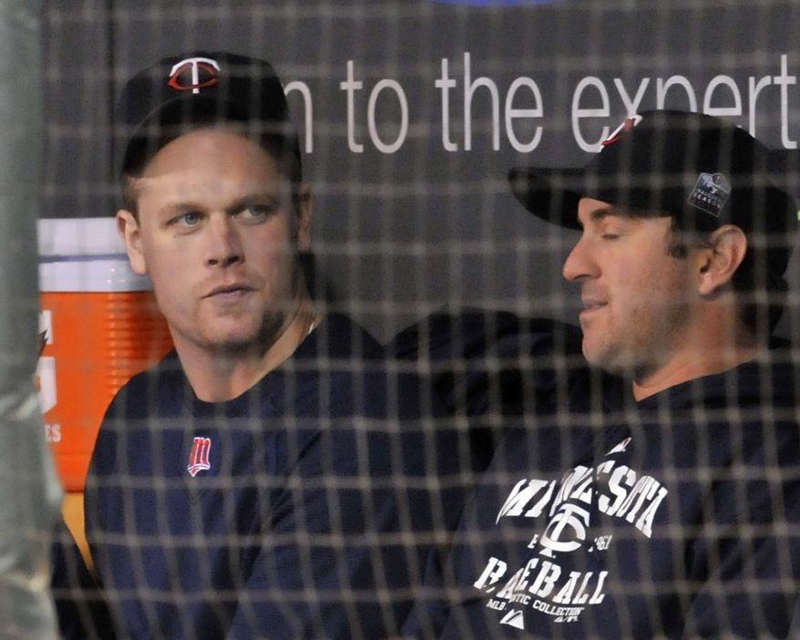 ASSOCIATED PRESS Minnesota Twins' Justin Morneau, left, takes in the baseball game against the Toronto Blue Jays from the dugout along with Nick Punto Thursday, Sept. 30, 2010, in Minneapolis.