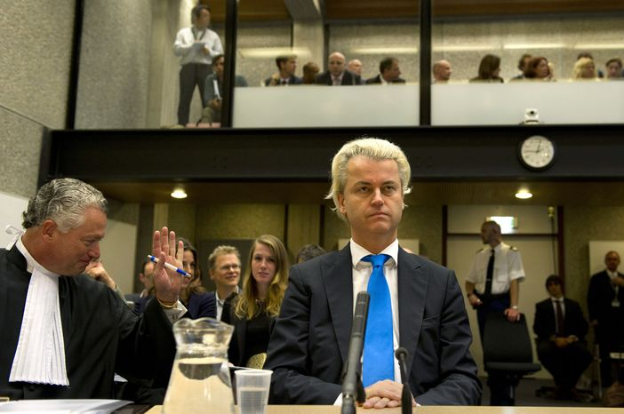 Dutch anti-Islam politician Geert Wilders, center, and his lawyer, Bram Moszkowicz, left, await the start of his trial inside the courtroom in Amsterdam, Netherlands, Monday, Oct. 4, 2010. (AP Photo/Marcel Antonisse, Pool)