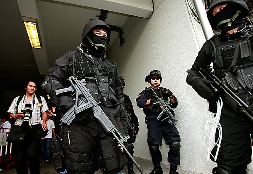 A unit of Thai commandos guard an entrance while providing security at the compound of a criminal court after the arrival of Viktor Bout, an alleged Russian arms smuggler, in Bangkok, Monday, Oct. 4, 2010. Bout arrived at the Bangkok court Monday in a bulletproof vest for a crucial hearing that could finally determine if he will be extradited to the United States.  (AP Photo/Apichart Weerawong)