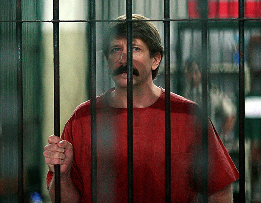 Alleged Russian arms smuggler Viktor Bout listens to a reporter's question from inside a cell at a criminal court in Bangkok, Monday, Oct. 4, 2010. Bout arrived at the Bangkok court Monday in a bulletproof vest for a crucial hearing that could finally determine if he will be extradited to the United States.  (AP Photo/Apichart Weerawong)