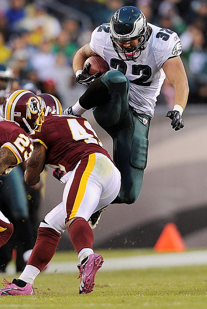 Philadelphia Eagles fullback Owen Schmitt leaps over Washington Redskins safety Kareem Moore during the second half of an NFL football game in Philadelphia, Sunday, Oct. 3, 2010. (AP Photo/Michael Perez)