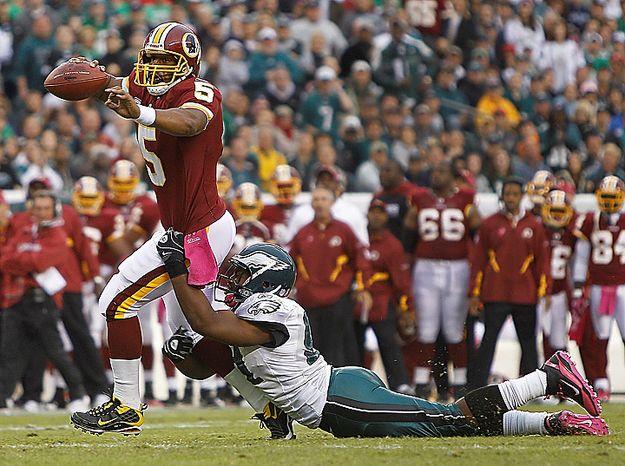 Washington Redskins quarterback Donovan McNabb drags Philadelphia Eagles defensive end Darryl Tapp with him as he scrambles for yardage during the first half of an NFL football game in Philadelphia, Sunday, Oct. 3, 2010. (AP Photo/Matt Slocum)