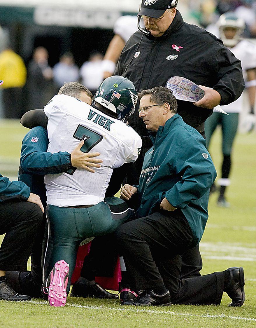 Philadelphia Eagles quarterback Michael Vick is supported by Eagle trainers as head coach Andy Reid listens after Vick was injured on a 23-yard scramble during first quarter game action in Philadelphia at Lincoln Financial Field August 13, 2010.  Michael Vick was injured on the play and left the game. UPI/John Anderson