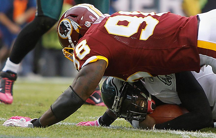 Washington Redskins linebacker Brian Orakpo lands on Philadelphia Eagles quarterback Michael Vick during the first half of an NFL football game in Philadelphia, Sunday, Oct. 3, 2010. (AP Photo/Matt Slocum)