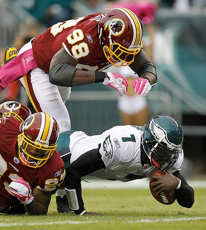 Philadelphia Eagles quarterback Michael Vick falls to the turf after being hit by Washington Redskins linebacker Brian Orakpo, top, and other Redskins defenders during the first half of an NFL football game in Philadelphia, Sunday, Oct. 3, 2010. Vick left the game after the play. (AP Photo/Mel Evans)