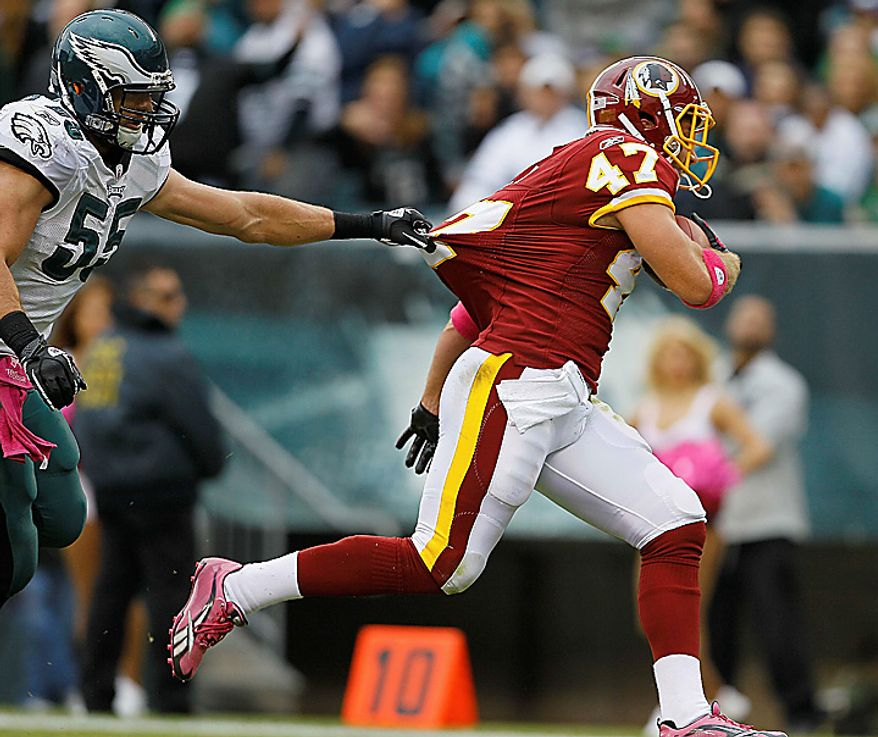 Philadelphia Eagles linebacker Stewart Bradley tries to hold on to Washington Redskins tight end Chris Cooley as he scores a touchdown during the first half of an NFL football game in Philadelphia, Sunday, Oct. 3, 2010. (AP Photo/Matt Slocum)