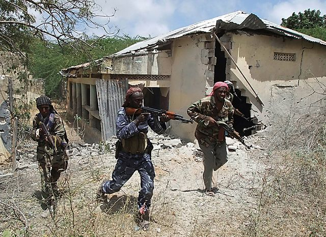 Islamist fighters take positions during clashes with Somali government soldier and African union peacekeepers in southern Mogadishu's Hodon neighborhood, Somalia,  Monday Oct. 4, 2010. Ali Muse, the head of Mogadishu's ambulance service, says a spike in violence the last three days in Mogadishu has killed at least 20 civilians. More than 70 people have been wounded. (AP Photo/Farah Abdi Warsameh)