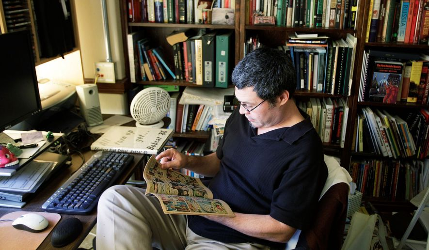 Jose Alaniz, an associate professor at the University of Washington in Seattle, sits in his office reading one of his favorite comic books, one of 10 he kept when he donated the rest of his collection to the library there. (Associated Press)
