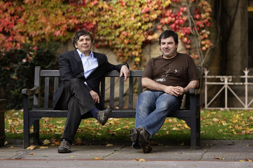 University of Manchester professors Andre Geim and Konstantin Novoselov, right, awarded the Nobel Prize for Physics pose for pictures outside Manchester University, Manchester, England, Tuesday, Oct. 5, 2010. (AP Photo/Jon Super).