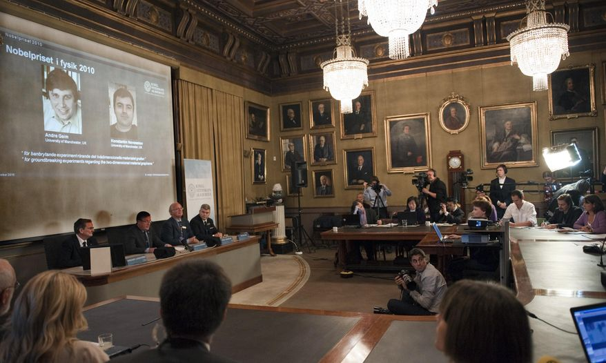 "Members of the Swedish Royal Academy of Sciences, left below screen, announce that Russian-born scientists Andre Geim, left on screen, and Konstantin Novoselov, right on screen behind podium, share the Nobel Prize in physics for ""groundbreaking experiments"" with an atom-thin material expected to play a large role in electronics in Stockholm, Sweden Tuesday Oct. 5, 2010 (AP Photo/Scanpix Sweden/Maja Suslin)"