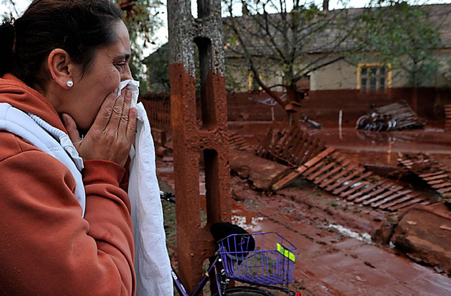 A Hungarian woman reacts while seeing her home flooded by toxic mud in the town of Devecser, Hungary, Tuesday, Oct. 5, 2010. Monday's flooding was caused by the rupture of a red sludge reservoir at an alumina plant in western Hungary and has affected seven towns near the Ajkai Timfoldgyar plant in the town of Ajka, 100 miles (160 kilometers) southwest of Budapest. (AP Photo/Bela Szandelszky)