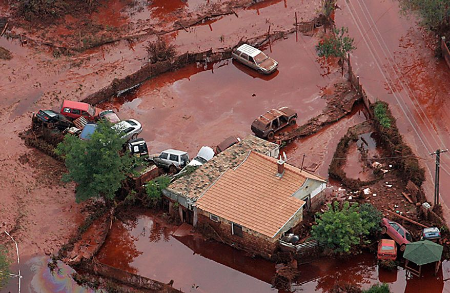 An aerial view shows overturned cars in the red sludge yard of a house in Kolontar, 167 kms southwest of Budapest, Hungary, taken on Tuesday, Oct. 5, 2010, after the wall of a reservoir containing slurry from an alumina factory in nearby Ajka broke, and over one million cubic meters of the poisonous chemical sludge inundated three villages.  (AP Photo/MTI, Gyoergy Varga)