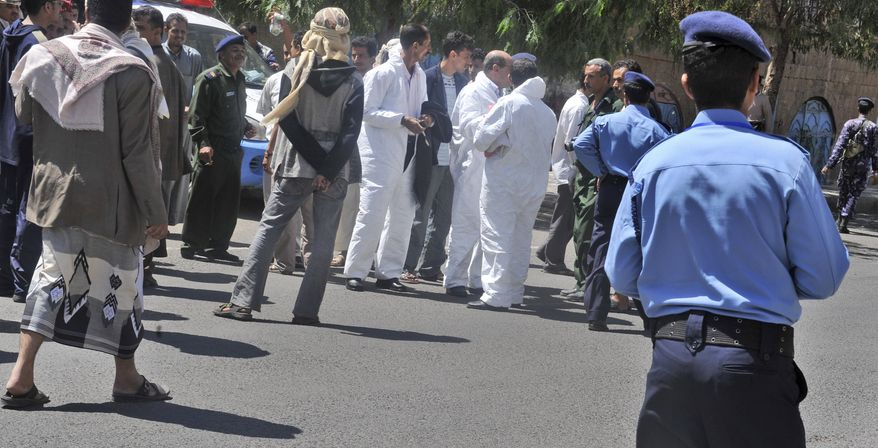 Yemeni security forces and forensics personnel attend the scene where an attack took place on a convoy carrying a senior British diplomat in capital San'a Wednesday, Oct. 6, 2010. (AP Photo)