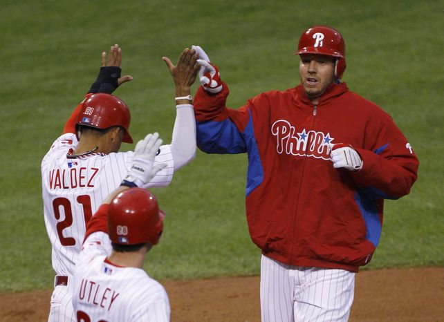 ASSOCIATED PRESS Philadelphia Phillies' Roy Halladay, right, celebrates after scoring against the Cincinnati Reds, with teammates Wilson Valdez (21) and Chase Utley during the second inning of Game 1 of baseball's National League Division Series, Wednesday, Oct. 6, 2010, in Philadelphia.