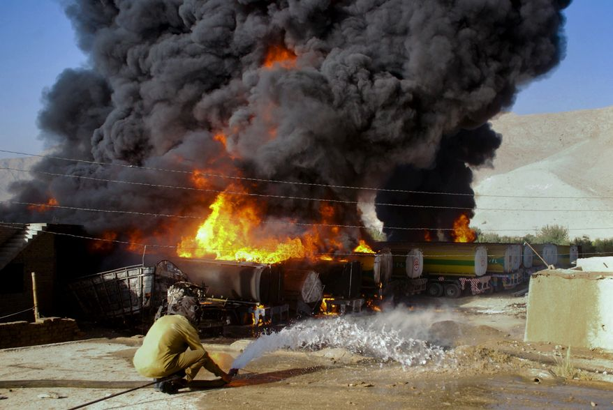 A Pakistani firefighter tries to extinguish burning oil tankers after militants attacked a terminal in Quetta, Pakistan, on Wednesday, Oct. 6, 2010. Gunmen in southwestern Pakistan torched a dozen tankers carrying fuel to NATO troops and killed a driver Wednesday, police said, the latest strike against supply convoys heading for Afghanistan since Pakistan shut a key border crossing last week. (AP Photo/Arshad Butt)