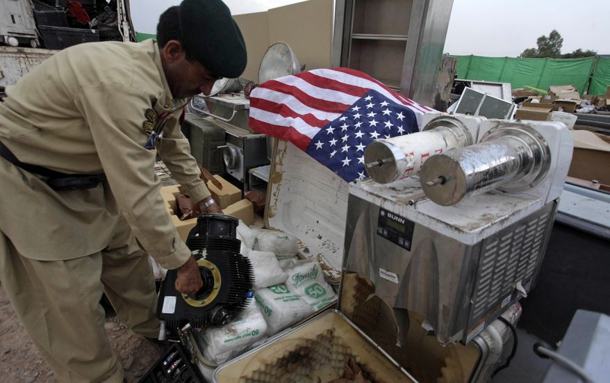 In this picture taken on Sept. 27, 2010, a soldier of Pakistani paramilitary force arranges equipment stolen from NATO trucks to display for the media in Peshawar, Pakistan. (AP Photo/Mohammad Sajjad)