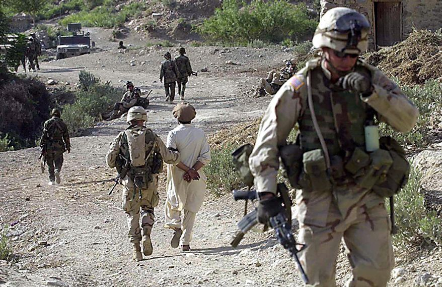 In this Sunday, Sept. 22, 2002 file picture, U.S. Army soldiers of Task Force Panther 82nd Airborne Division take a local man suspected of sheltering al-Qaida members into questioning after seaerching a compound in the southeast region of Afghanistan. (AP Photo/Wally Santana, File)