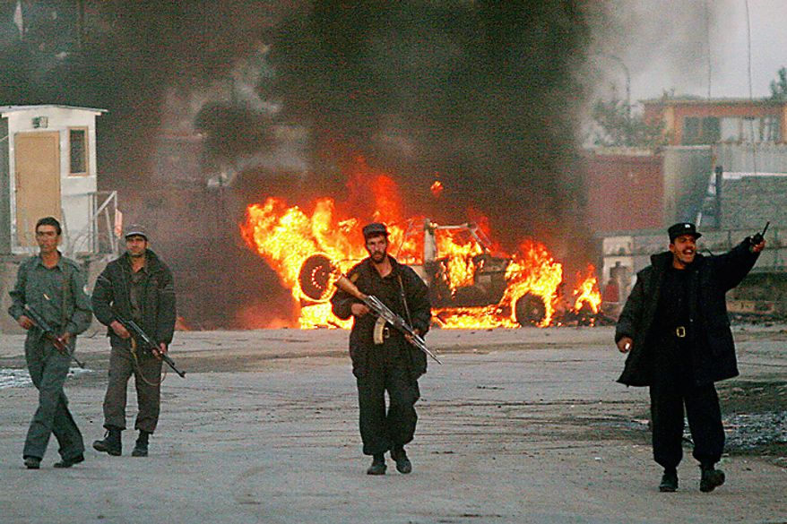In this Monday, Nov. 14, 2005 file picture, police officers secure the area in front of a burning international peacekeeper vehicle after a second suicide attack in Kabul, Afghanistan, and just minutes before a third attempt in the same site. Two separate suicide attackers rammed cars laden with explosives into NATO peacekeepers in the Afghan capital, killing at least one German soldier and wounding eight other people. Peacekeepers opened fire to thwart a suspected third bombing attempt, killing three people. (AP Photo/Tomas Munita, File)