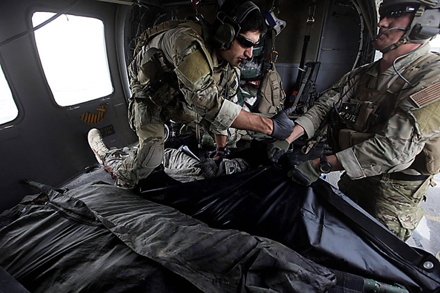 In this Thursday July 29, 2010 file picture, Tech. Sgt. Jeff Hedglin, right, and Senior Airman Robert Dieguez, both U.S. Air Force Pararescuemen, or PJs, place into a body bag, the remains of one of two U.S. soldiers killed minutes earlier in an IED attack, as soldiers, unseen wait to carry them away, upon landing after a helicopter rescue mission in Kandahar province, southern Afghanistan. (AP Photo/Brennan Linsley, File)