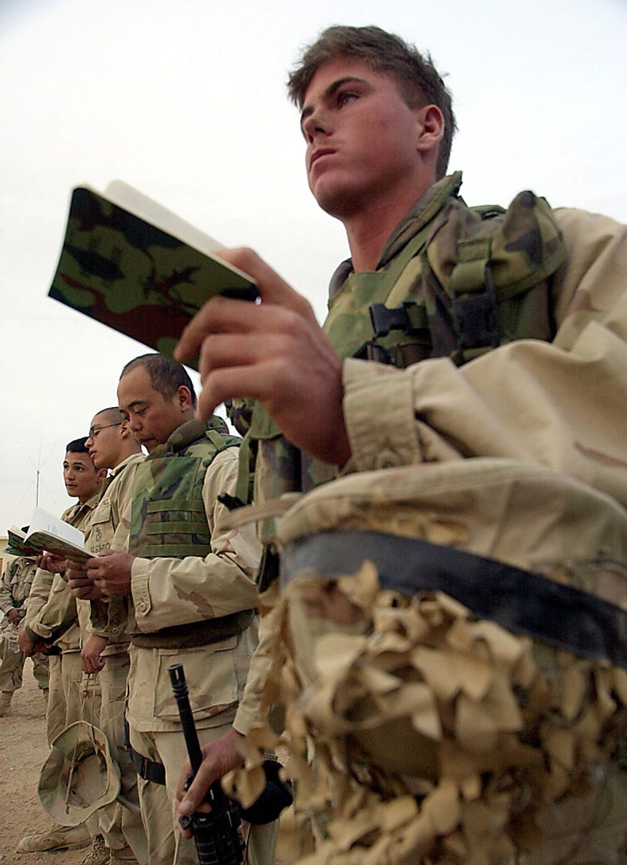 In this Wednesday, Dec. 12, 2001 file picture, Marine Lance Cpl. Chris McNeely, right, of Whiting, Kan., holds his battlefield hymnal as he attends a memorial service at Camp Rhino in southern Afghanistan, to commemorate the three-month anniversary of the Sept. 11 terrorist attacks in the United States. (AP Photo/Dave Martin, Pool, File)