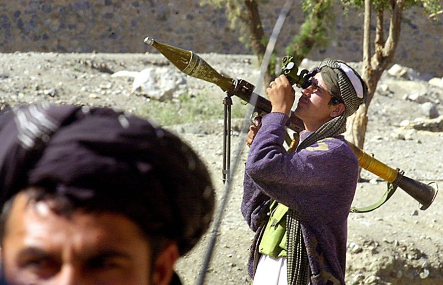 In this Monday, Oct. 15, 2001 file picture, a Taliban soldier scans the sky as he holds a rocket launcher at the Torkham border crossing between Afghanistan and Pakistan. (AP Photo/Enric Marti, File)