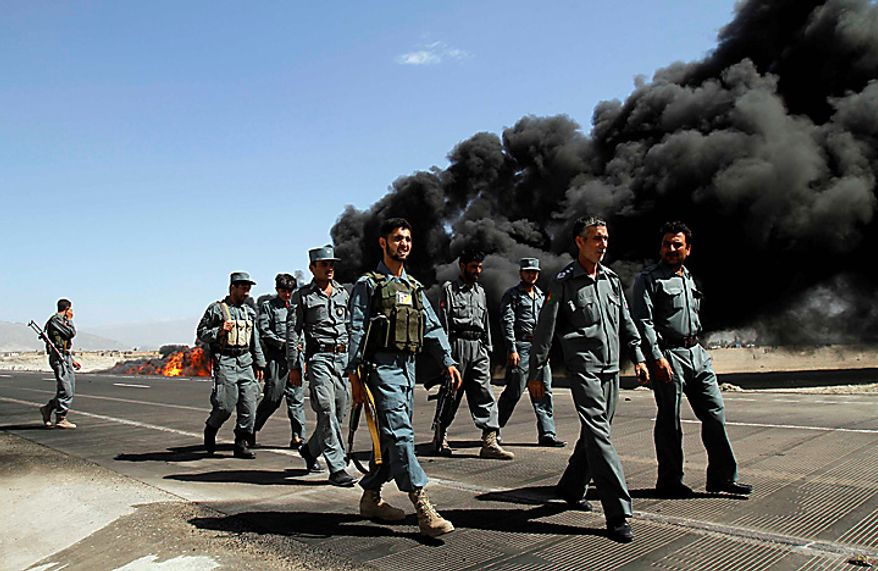 In this Friday, May 28, 2010 file picture, police officers walk past a burning oil tanker carrying fuel supplies for NATO forces after it was attacked on Jalalabad highway, east of Kabul, Afghanistan. (AP Photo/Rahmat Gul, File)