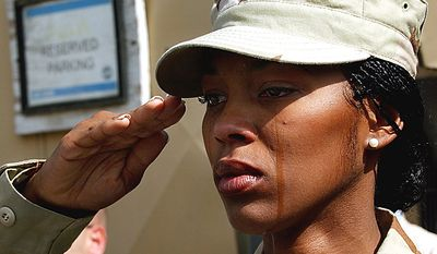 In this Monday, Sept. 11, 2006 file picture, tears run down the cheeks of U.S. Staff Sgt. Alicia Watkins from Washington D.C. as she salutes during a ceremony marking the fifth anniversary of the Sept. 11 attacks at a U.S. military base in Kabul, Afghanistan. (AP Photo/Musadeq Sadeq, File)