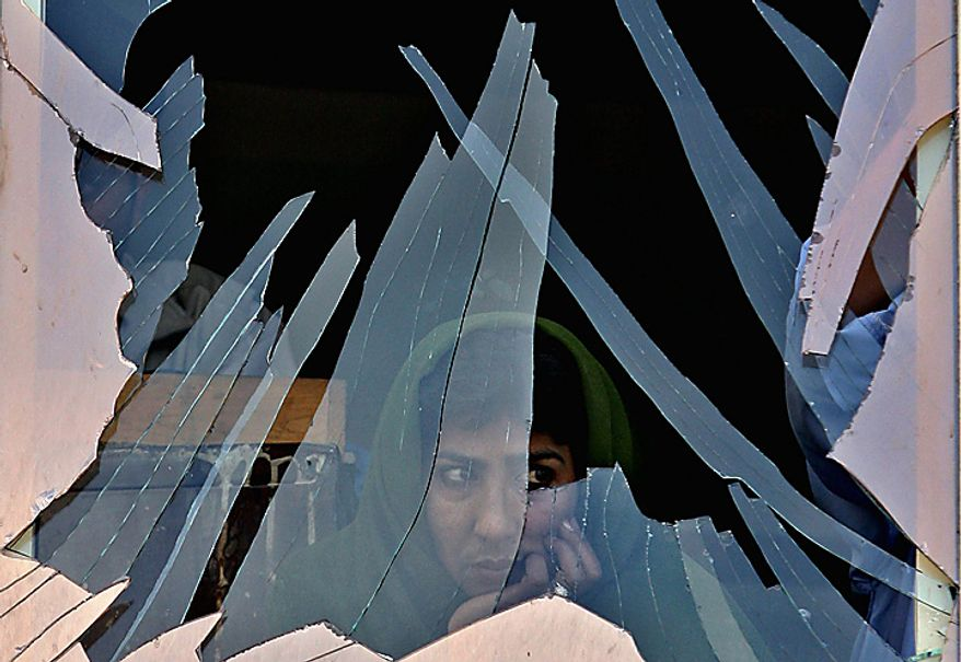 In this Tuesday, July 4, 2006 file picture, a woman looks out through a destroyed window after a bomb exploded in Kabul, Afghanistan in front of a cinema near the presidential palace, wounding at least four people, police said. (AP Photo/Rodrigo Abd, File)