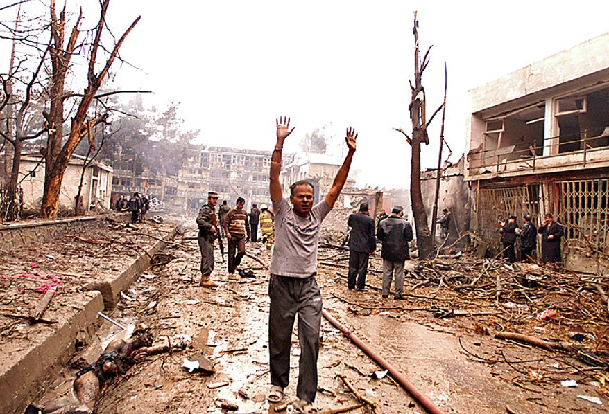 In this Friday, Feb. 26, 2010 file picture, an unidentified man raises his hands as he walks away from the scene of an explosion at a guesthouse in Kabul, Afghanistan. (AP Photo/Ahmad Massoud, File)