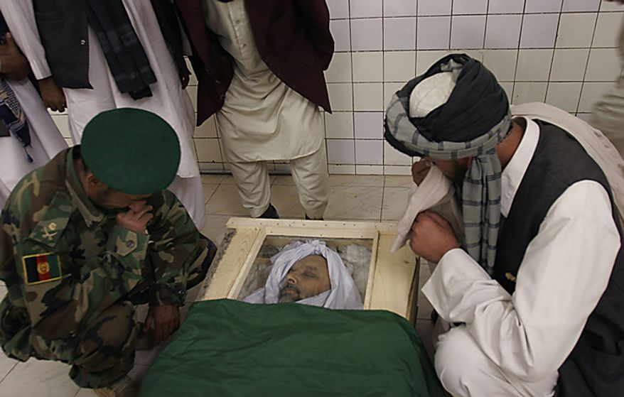 In this Monday, April 28, 2008 file picture, relatives mourn over the body of lawmaker Fazel Rahman Samkanai at the hospital in Kabul, Afghanistan. Samkanai, who was about 30 yards away from President Hamid Karzai, was killed when suspected Taliban militants attacked a ceremony marking the 16th anniversary the defeat of the Soviet invasion of Afghanistan in Kabul on Sunday. (AP Photo/Rahmat Gul, File)