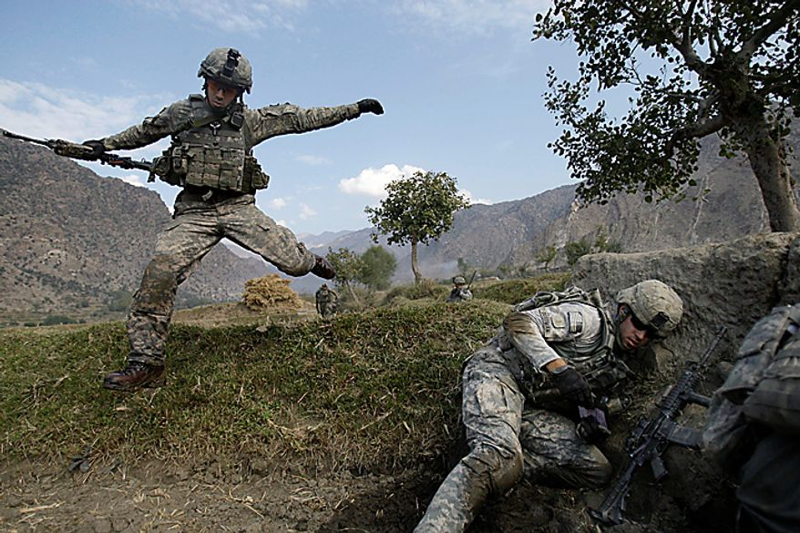 In this Nov. 3, 2009 file photo, Cpl. Casey Liffrig, left, leaps for cover as Lt. Thomas Goodwin gets down as Taliban fighters ambush U.S. soldiers from the 2nd Battalion, 12th Infantry Regiment, 4th Brigade Combat Team, 4th Infantry Division during a patrol in the Pech Valley of Afghanistan's Kunar province. (AP Photo/David Guttenfelder, File)