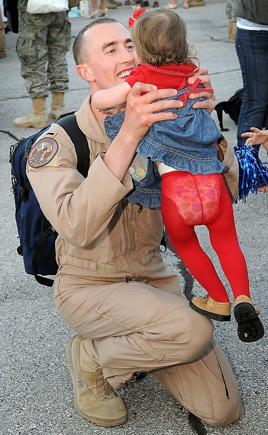 In this Wednesday, July 28, 2010 file picture, Lt. Matt Fryer smiles as he lifts his one-and-a-half-year-old daughter Clarity on the tarmac at Ellsworth Air Force Base, S.D. Lt. Fryer was among 350 airmen returning home to the South Dakota airbase after being deployed in Southeast Asia for six months in support of the 28th Bomb Wing whose B-1 bombers supply long-range and close air support to the troops in Iraq and Afghanistan. (AP Photo/Steve McEnroe, File)